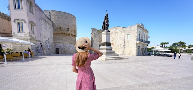 Panoramic wide angle of young woman in long dress walking in otranto historic town, italy
