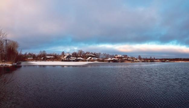 雪に覆われた湖の近くの古い家とパノラマの冬の景色。冬の本格的な北部の都市ケム。ロシア。