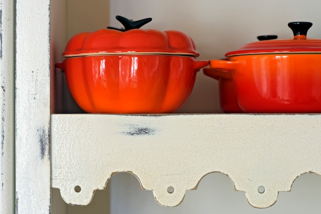 Pans of refractory porcelaine on white cabinet shelf