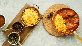 Pans with rice and spices on boards