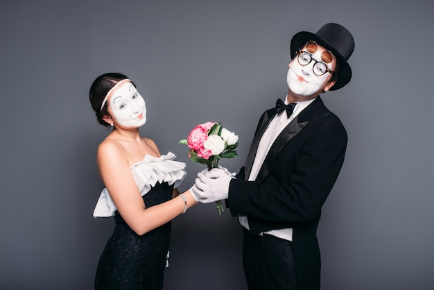 Pantomime actor and actress performing with flower bouquet. mime theater performers posing.