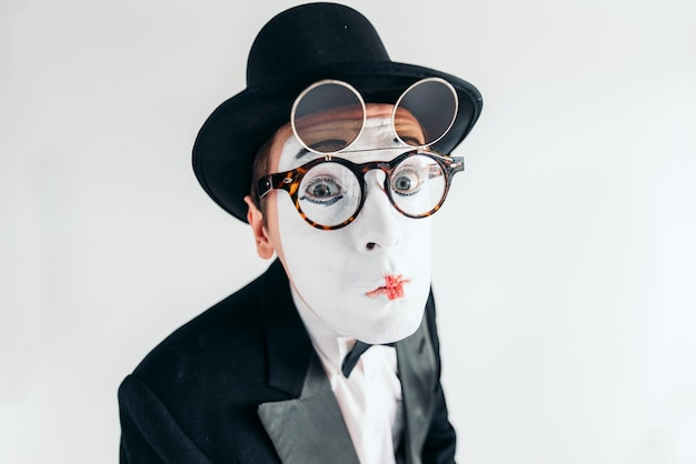 Pantomime actor face in glasses and makeup mask. mime in suit, gloves and hat.