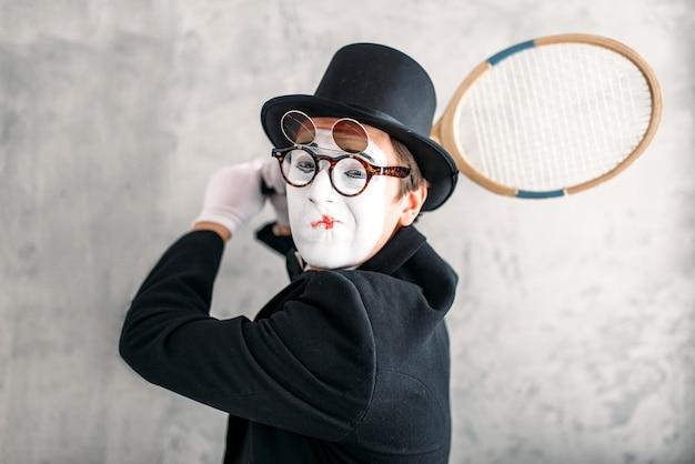 Актер пантомимы выступает с ракеткой для бадминтона. комедийный артист пантомимы в костюме, перчатках, очках, маске для макияжа и шляпе