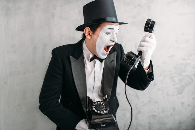 Pantomime actor performing with retro telephone