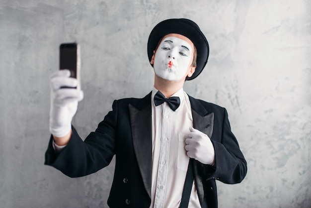 Pantomime actor with makeup mask makes selfie on camera. comedy artist in suit, gloves and hat