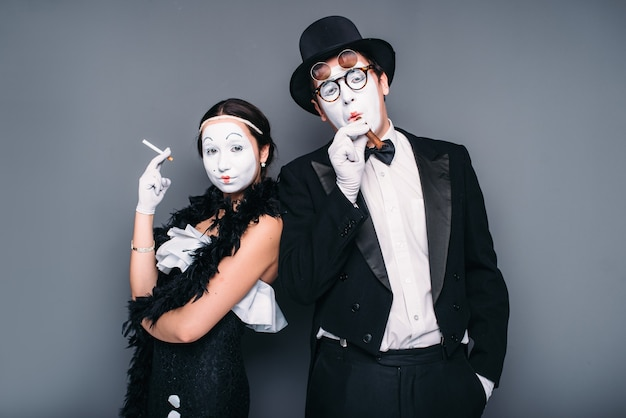 Pantomime actors posing with cigar and cigarette. comedy artist and actress performing.
