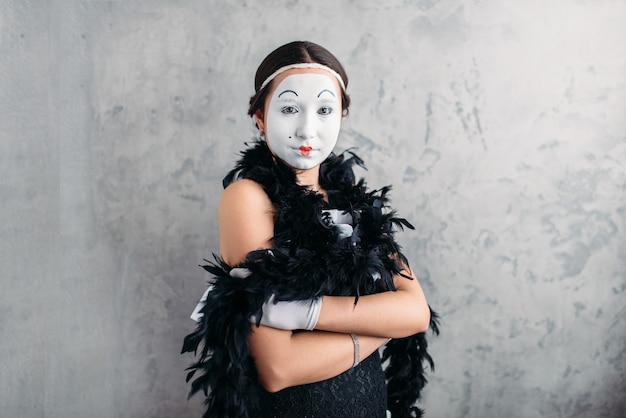 Pantomime actress with white makeup mask posing in studio.