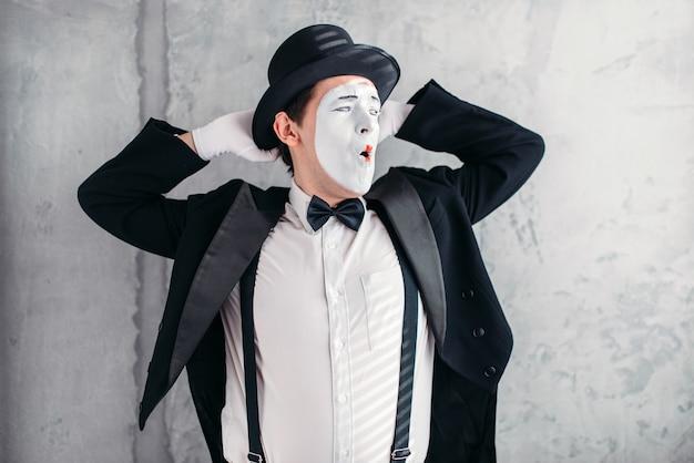 Художник-пантомима с маской для макияжа. мим в костюме, перчатках и шляпе.