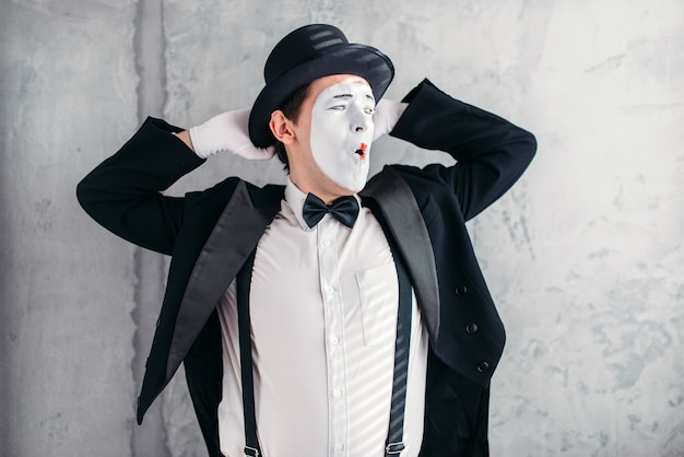 Pantomime artist with makeup mask. mime in suit, gloves and hat.
