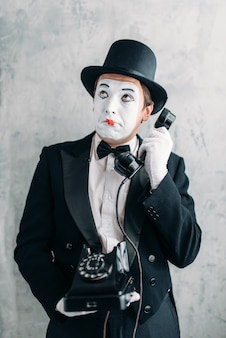 Pantomime theater actor with makeup mask performing with retro telephone.