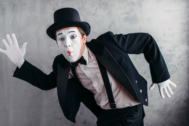 Pantomime theater artist posing, mimic male person with white makeup mask.