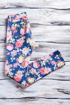 핑크 플라워 프린트의 팬츠. 세련된 패턴의 여성용 팬츠. 바닥에 옷 조각입니다. 저렴한 가격에 고품질 의류.