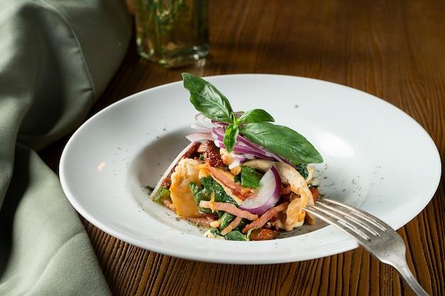 Panzanellaまたはpanmolle-木製の背景に浸した古いパン、玉ねぎ、トマトinwhiteボウルの人気のイタリアみじん切りサラダのビューを閉じます。平置き食品