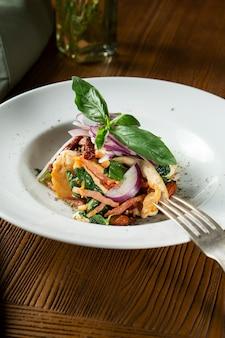 Закройте вверх по взгляду на panzanella или panmolle - популярном итальянском прерванном салате выдержанного несвежого хлеба inwhite хлеба, луков и томатов на деревянной предпосылке. плоская кладка еды