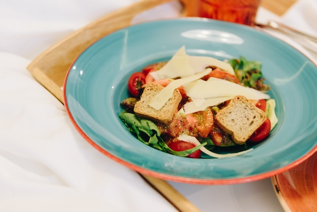 Panzanella with croutons and cheese on a blue plate on a tray as a meal in bed