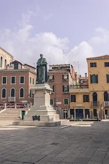 Статуя паоло сарпи в венеции и другое историческое здание позади