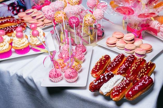 과자를위한 테이블에 pap-cakes, eclairs, 케이크 및 마카로니