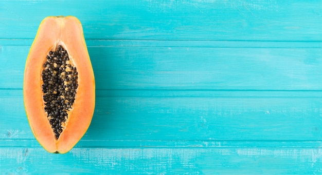 Papaya cut in half on blue wooden background. copy space. top view.