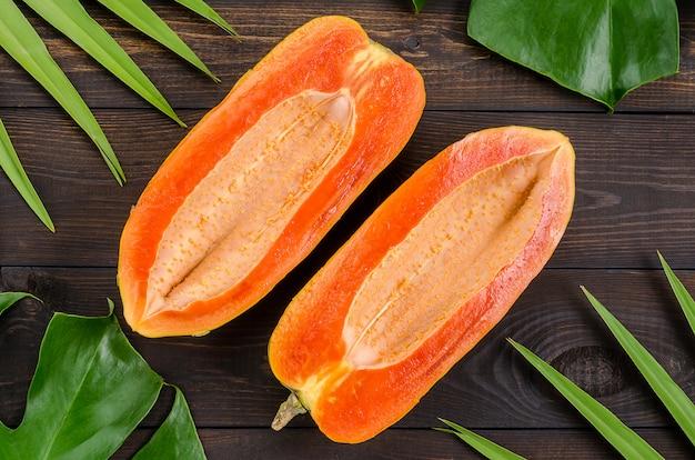 Papaya cut in half on a dark wooden background.