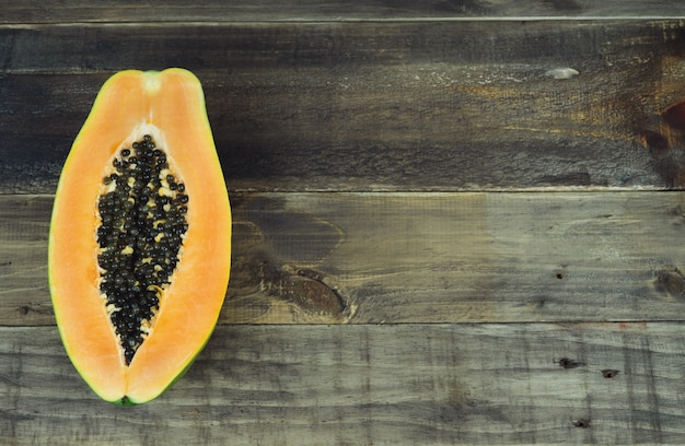 Papaya cut in half on wooden background. copy space. top view.