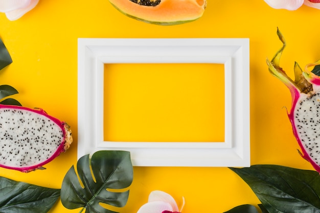 Papaya; dragon fruit; leaves around the empty white border frame against yellow backdrop
