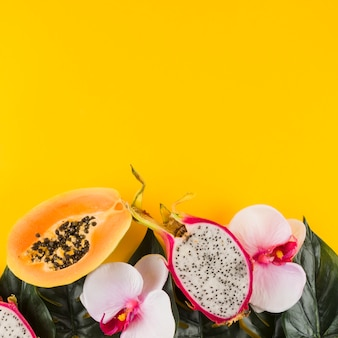 Papaya; dragon fruit; leaves and orchid flower against yellow backdrop