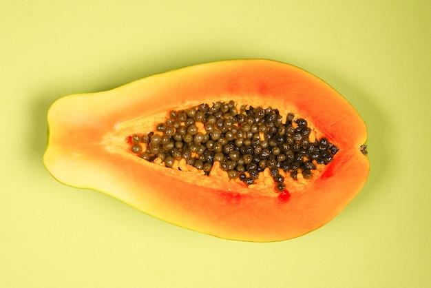 Плоды папайи на зеленом фоне. тропический фрукт. половина папайи.