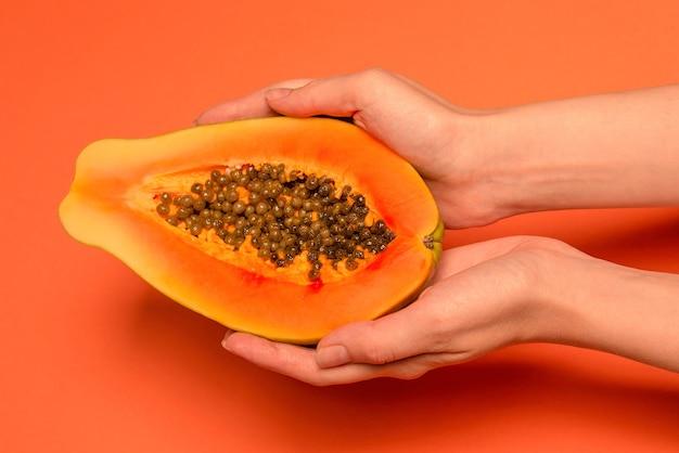 Плоды папайи на оранжевом фоне в руках женщины. тропический фрукт. половина папайи.