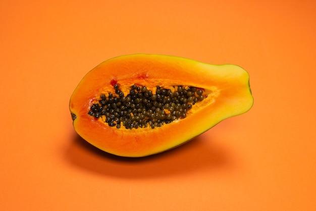 Плоды папайи на оранжевом фоне. тропический фрукт. половина папайи.