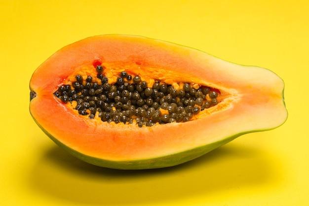 黄色の背景にパパイヤフルーツ。トロピカルフルーツ。ハーフパパイヤ。