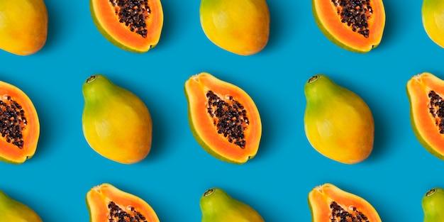 Бесшовный узор из папайи на синем цвете Premium Фотографии