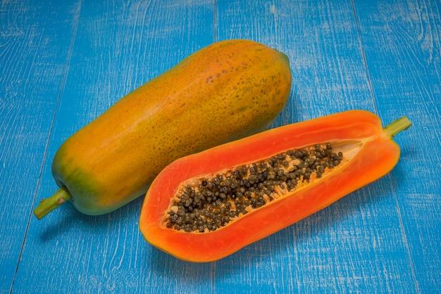 パパイヤの果実、全体と青い木製のテーブルの種子と熟したパパイヤの果実の半分。