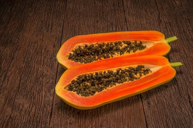 パパイヤの果実、全体と木製のテーブルの種子と熟したパパイヤの果実の半分。