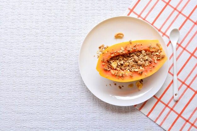 Плоды папайи с мюсли на тарелке в столе