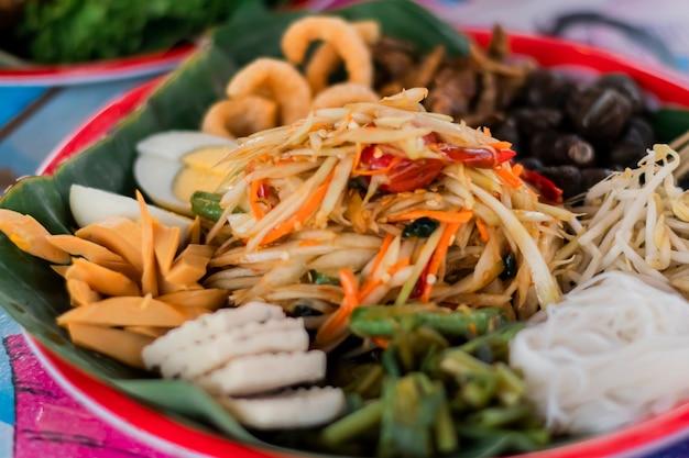 Салат из папайи и различные начинки разложены на подносе.