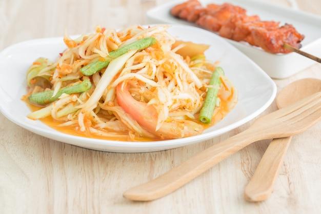 木製のテーブル上の白いプレートのパパイヤサラダ、ローカルタイ料理
