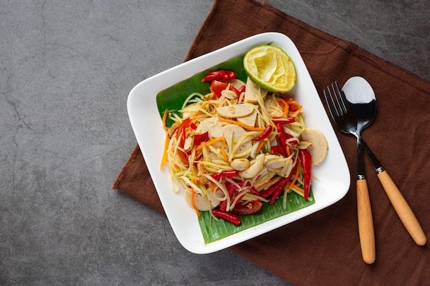 Салат из папайи, подается с рисовой лапшой и овощным салатом. украшен ингредиентами тайской кухни.