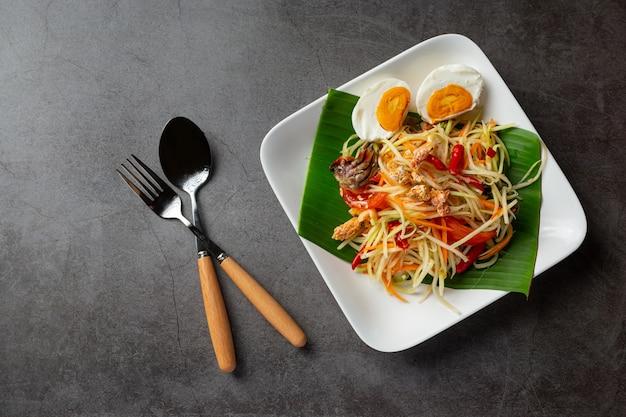 Insalata di papaya servita con spaghetti di riso e insalata di verdure decorata con ingredienti alimentari tailandesi.