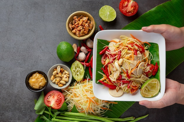 Papaya salad served with rice noodles and vegetable salad decorated with thai food ingredients.