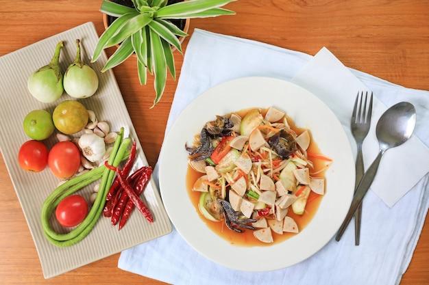 Салат из папайи (сом там) традиционные тайские продукты на фоне деревянного стола. самая востребованная популярная еда в таиланде