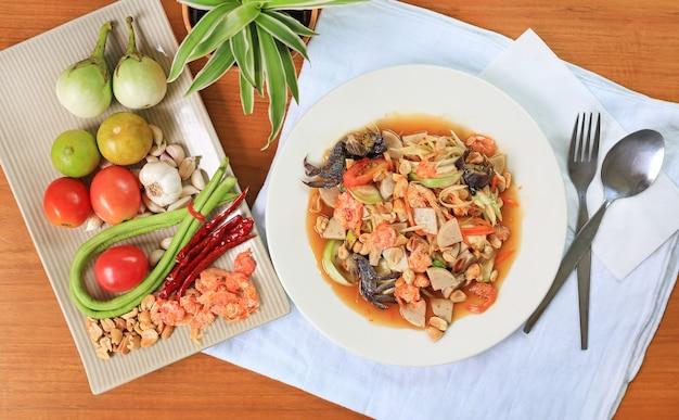パパイヤサラダ(ソムタム)木製のテーブルの背景に伝統的なタイ料理。