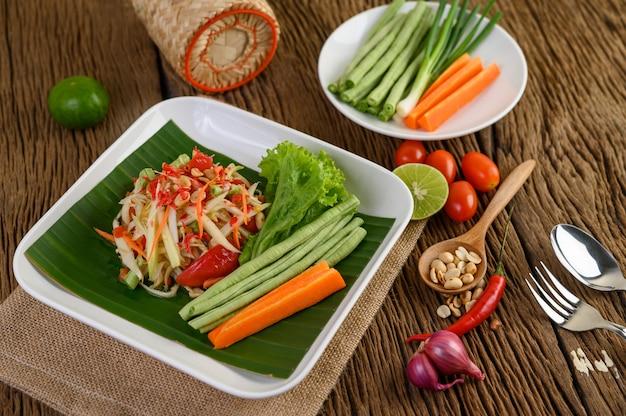 Салат из папайи (som tum thai) на белой плите на деревянном столе.