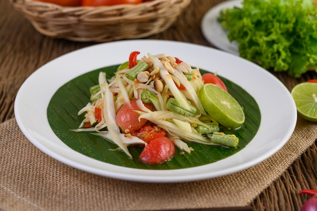 Papaya salad (som tum thai) on a white plate on a wooden table.