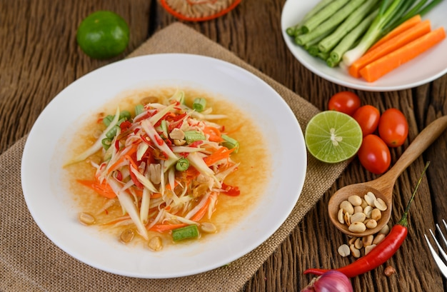 Papaya salad (som tum thai) on a white plate on a wooden table.