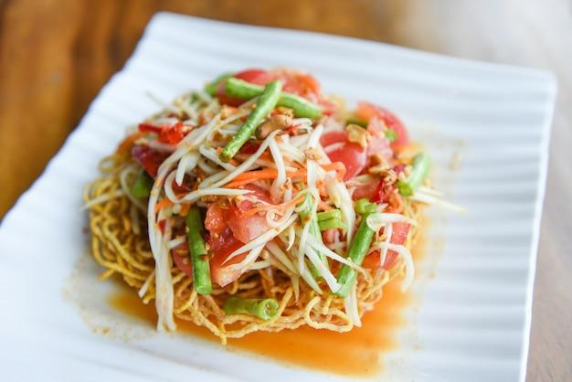 Салат из папайи острый на хрустящей лапше на белой тарелке
