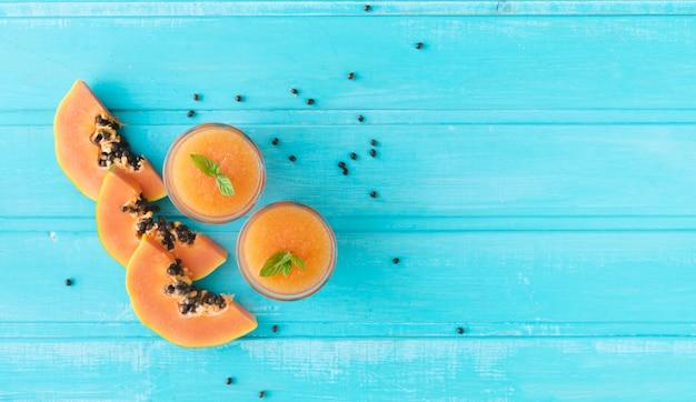 Ломтики папайи. синий фон из деревянных досок. скопируйте пространство. вид сверху.