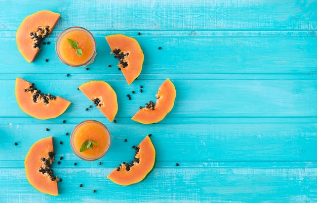 Papaya slices. blue background of wooden planks. copy space. top view.