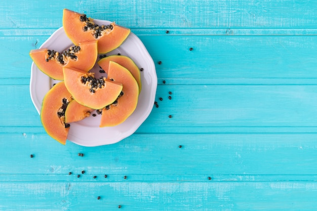 Papaya slices on plate on blue wooden background. copy space. top view.