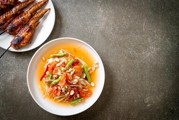 グリルドチキンのパパイヤスパイシーサラダ-タイの伝統的な屋台の食べ物のスタイル
