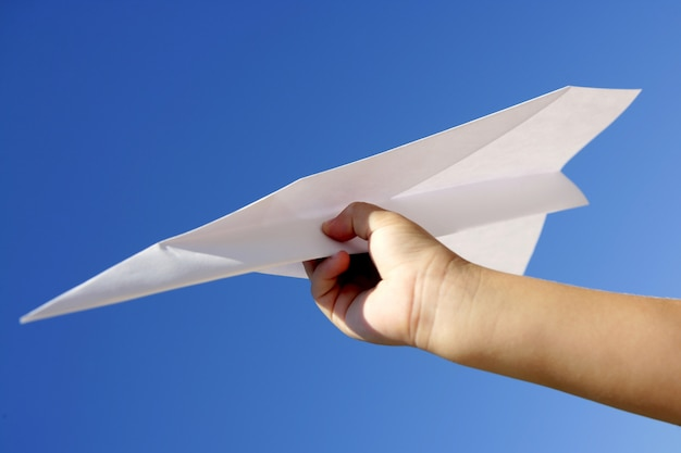 Paper airplane in children hand over blue sky